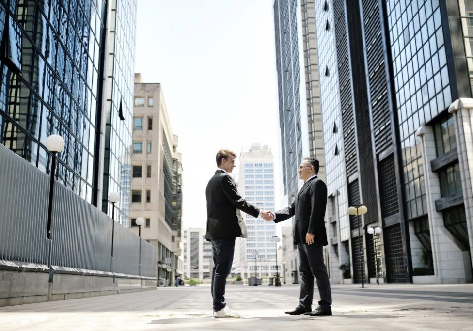 two businessmen shaking hands on background modern office corporate buildings